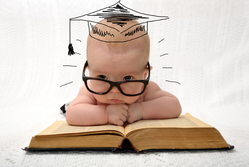 cute little baby in glasses with painted professor hat lieing on old book on light background