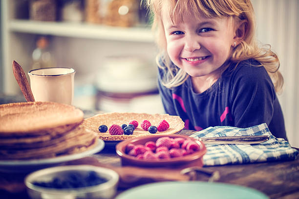 Cute little girl eating homemade traditional dutch pannenkoeken (pancakes) with fresh berries. CNEUFOO595